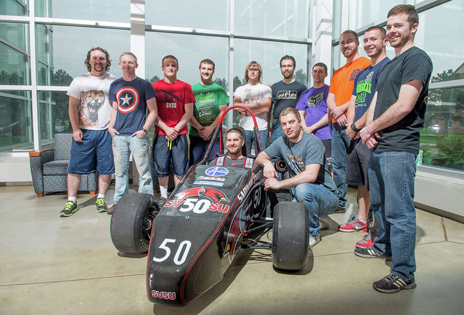 Members of the Saginaw Valley State University Cardinal Formula Racing team are shown with the vehicle they designed.