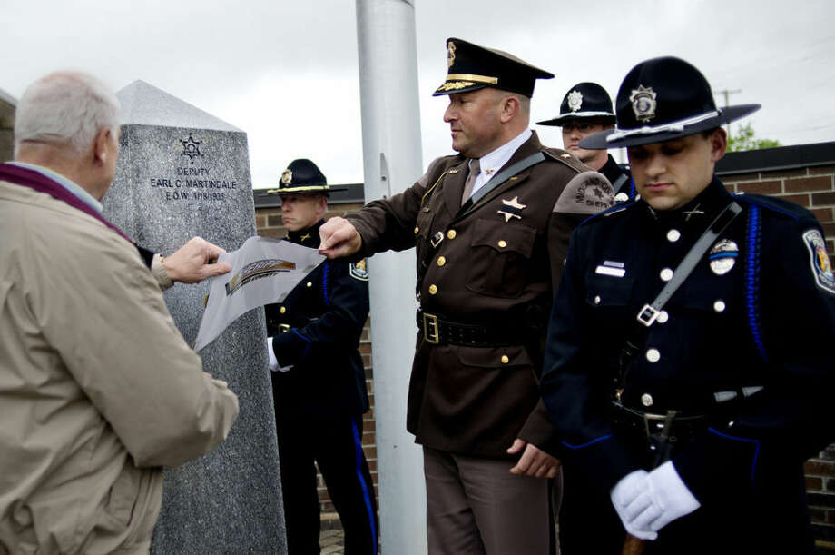 NICK KING | nking@mdn.netMidland County Sheriff Scott Stephenson, center right, and former sheriff Jerry Nielson, left, unveil the name of Midland Sheriff's Deputy Earl C. Martindale on the Midland Law Enforcement Memorial Thursday during a Peace Officers Memorial Day ceremony at the Midland Law Enforcement Center. Martindale died in the line of duty in 1935. The ceremony was held to honor peace officers currently serving their communities and those who have lost their lives. Members of the Midland Police Honor Guard, from left, Lt. Matthew Berchert, Scott Coyle and Eddie Hinson, look on. Photo: Nick King/Midland  Daily News