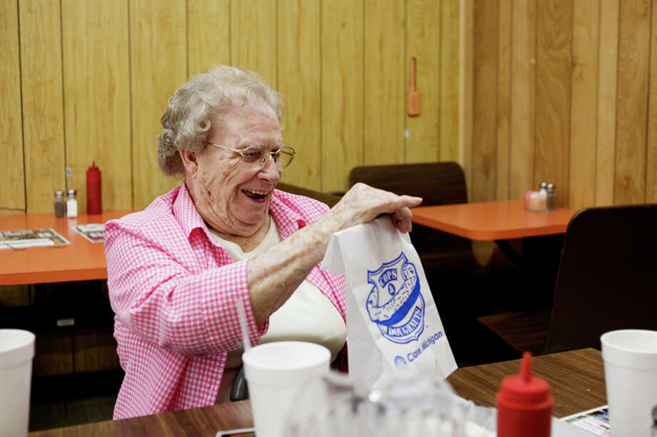 "Vivian Yaxley, 97, smiles after getting a lemon donut from Cops and Donuts at Sid's Party Store in Midland on Wednesday. Yaxley, who now lives in Riverside Place, was born in Indiana in 1917 in Indiana and moved with her family to the Gladwin area when she was 2. ""It's work,"" Yaxley said about living a long life. ""You keep busy and you don't sit in a chair."" Yaxley wanted to eat a hamburger at Sid's for her birthday lunch and she ate with her daughters, Sharon Phillips and JoAnn Duford and their husbands Rusty and Jerry. Her granddaughter, Julie Parlett also met them for lunch. Photo: Neil Blake/Midland Daily News / Midland Daily News"