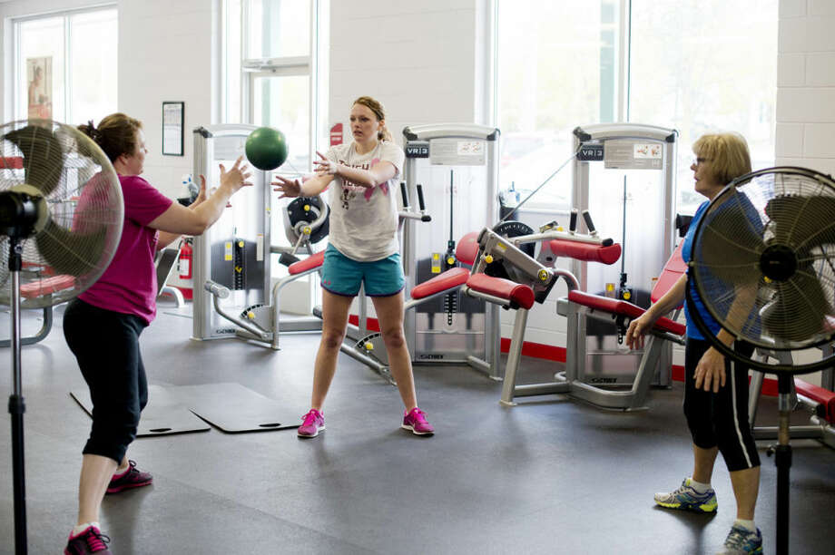 From left, Jamie Howe, Ali Howe and Cheryl Draves work out at Snap Fitness in Midland with trainer Phil Cosens (not pictured). Cheryl is Jamie's mother and Jamie is Ali's mother. Photo: NEIL BLAKE | Nblake@mdn.net