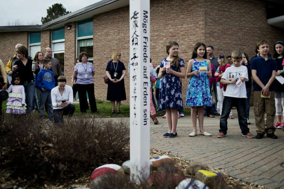"NEIL BLAKE | nblake@mdn.netStudents and parents stand by during the dedication ceremony for the peace pole at Adams Elementary School on Wednesday. The peace pole has eight languages on it that say the words, ""May peace prevail on the Earth."" The dedication was part of Adams' 50th anniversary celebration. Photo: Neil Blake/Midland Daily News"
