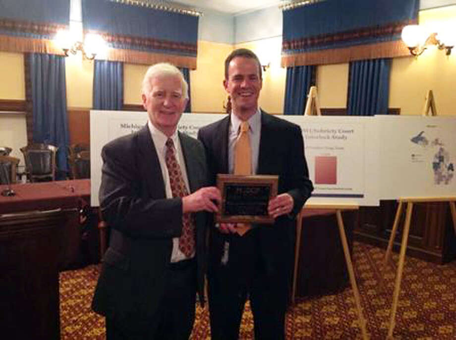 Judge Hoffman of Eaton County, on behalf of the Michigan Association of Drug Court Professionals, presents state Rep. Kevin Cotter, right, with the Legislator of the Year award. Photo: Photo Provided