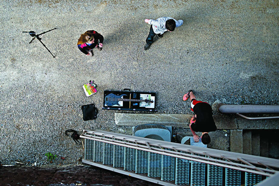 SEAN PROCTOR | sproctor@mdn.net From left; Rebecca Singer, Nick Shahin and Nick Lambert, all seniors at Midland High School, work on filming a music video for their final project in Kendall Root's calculus class on Friday afternoon in the alley behind Oscar's Bar & Grill. The group, along with classmate Thor Russell, wrote original music and lyrics talking about the struggles of learning calculus combined with brief anecdotes from the semester. They started writing the song about a week and a half ago, and started filming on Thursday. The project is due on Tuesday. Photo: Sean Proctor/Midland  Daily News