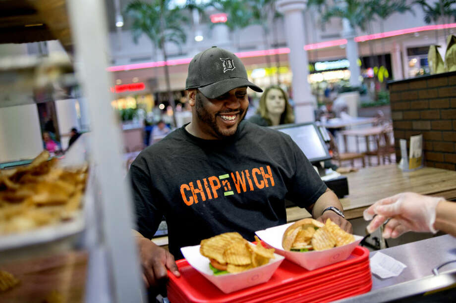 NICK KING | nking@mdn.netChip-n-Wich co-owner Jonathan Neely, left, grabs a customer's order at the sandwich shop at the Midland Mall food court. Photo: Nick King/Midland  Daily News