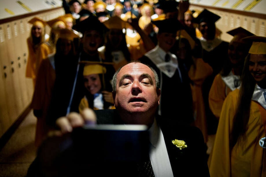 Bullock Creek School District superintendent Charles Schwedler takes a picture of himself with graduating class behind him Friday during the Bullock Creek High School graduation ceremony. 139 seniors walked during the ceremony. Photo: Sean Proctor/Midland Daily News