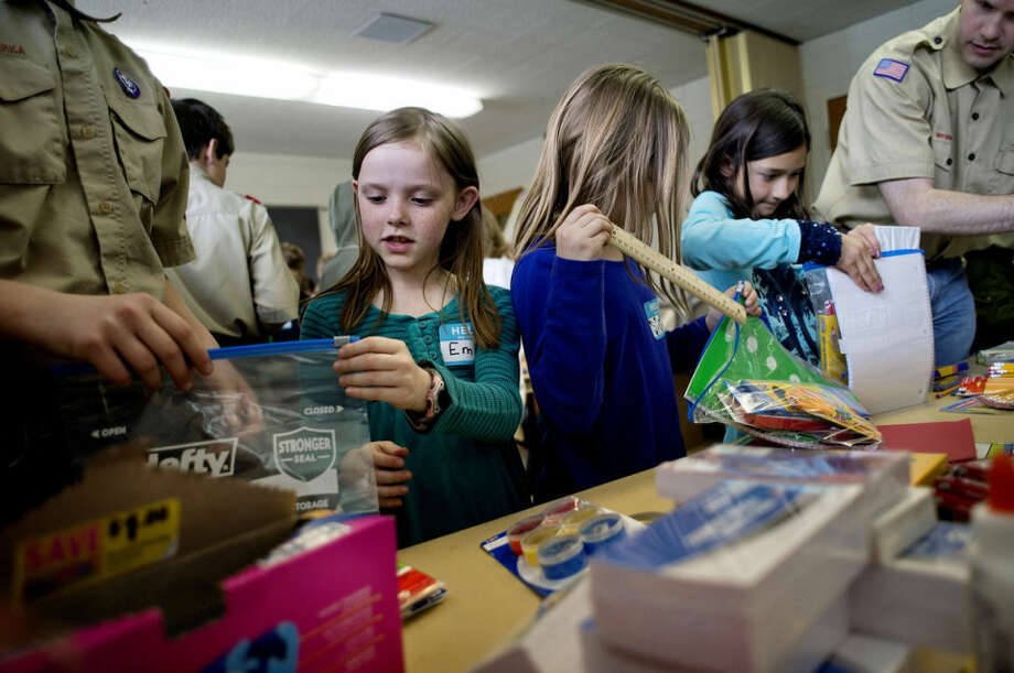 From left, Boy Scout Troop 787 member Nathan Herzog, 13, Emily Roy, 9, Sydona Parks, 9, Anna Martinez, 9, and troop leader and congregation bishop Sasha Savage pack kits of school supplies as part of Jacob Krueger's Eagle Scout project Saturday at the Church of Jesus Christ of Latter-day Saints in Midland. Over the course of a month, Jacob collected donated school supplies including notebooks, pencils, rulers, scissors, etc., in order to make kits to send to schools in the Philippines. Children 8 to 11 years old and members of Boy Scout Troop 787 participated in getting the kits together at the church. Photo: Nick King/Midland  Daily News