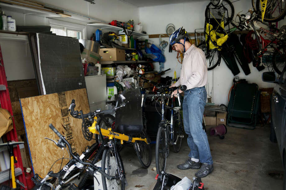 NEIL BLAKE | nblake@mdn.netJosh Stevens parks his bicycle in his garage after cycling to work. Photo: Neil Blake/Midland Daily News