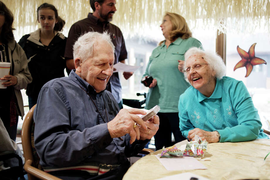 Emil Schmidt, 102, opens one of his gifts while sitting next to his sister on his birthday at MidMichigan Stratford Village on May 14. The gift was playing cards with the presidents of the United States on them. Schmidt was born in 1912 is a WWII veteran. Photo: Neil Blake/Midland Daily News / Midland Daily News
