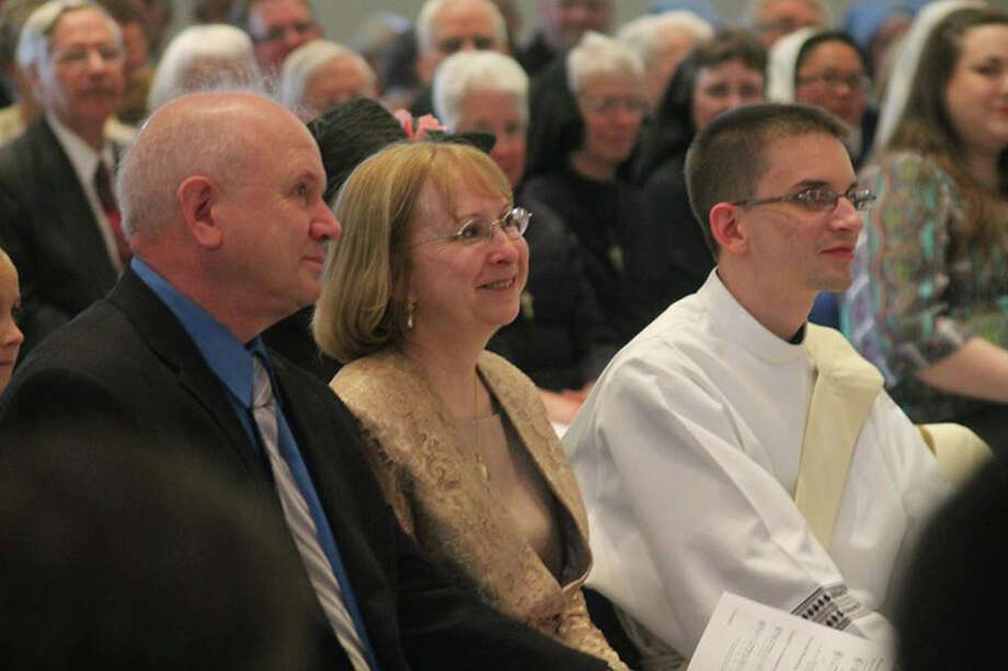 Father Andrew LaFramboise sits with his parents, Bill and Kathy LaFramboise, during his ordination service.
