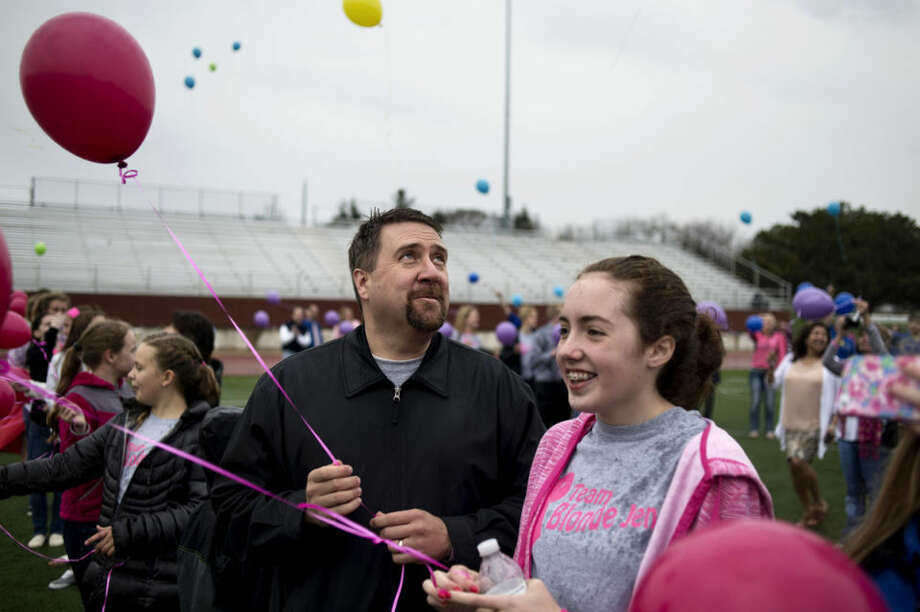 "Mike Sisco looks skyward as he stands with his daughter, Lauren, 14, during a balloon launch of rainbow colors in honor of Mike's wife and Lauren's mother, Jenifer Sisco, following her memorial service at Midland High School on Wednesday. Sisco, a math teacher at Midland High, died last Friday after a three year battle with cancer. ""Midland High is a great place,"" Eric Albright, the school's athletic director, said. ""Jen Sisco made it better."" Photo: Neil Blake/Midland Daily News"