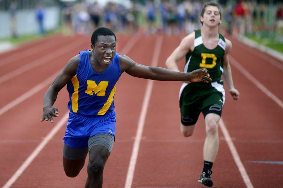 NICK KING | nking@mdn.netMidland's Vondre Warren, left, crosses the finish line as Dow's Ben Deruyter closes in during the 100 meter dash Tuesday at Dow High School. Photo: Nick King/Midland  Daily News