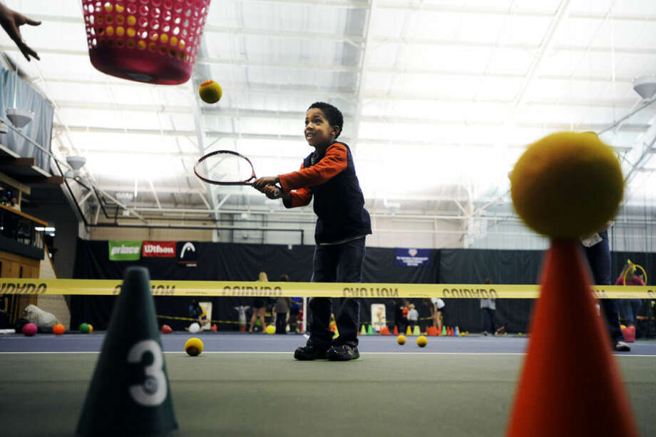 Andrew Himmer, 5, of Midland, practices his tennis swing in the activities area at the Midland Community Tennis Center's 40th anniversary on Friday afternoon. Activities included face painting, one-on-one tennis matches and a bounce house. Photo: ZACK WITTMAN | For The Daily News