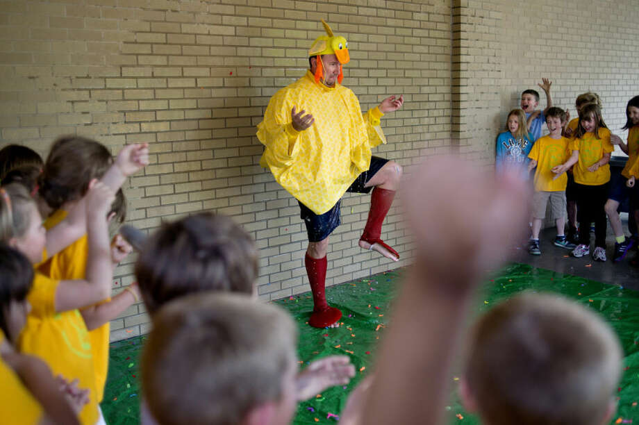 Dressed as a duck, Principal Lon Medd, center, anticipates a water balloon thrown by a student Wednesday outside Saint Brigid Catholic School. Photo: NICK KING | Nking@mdn.net
