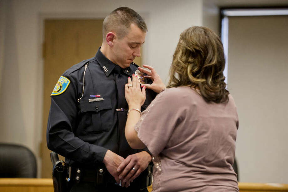 NEIL BLAKE | nblake@mdn.netFelicia Coney pins the Midland Police Department badge on her husband, Eric Coney, during his swearing in ceremony at Midland City Hall on Tuesday. Charles Brown and Brennon Warren were also sworn in during the ceremony. Coney was born and raised in Beaverton and worked at the Gladwin County Sheriff's Office before coming to the Midland Police Department. Photo: Neil Blake/Midland Daily News