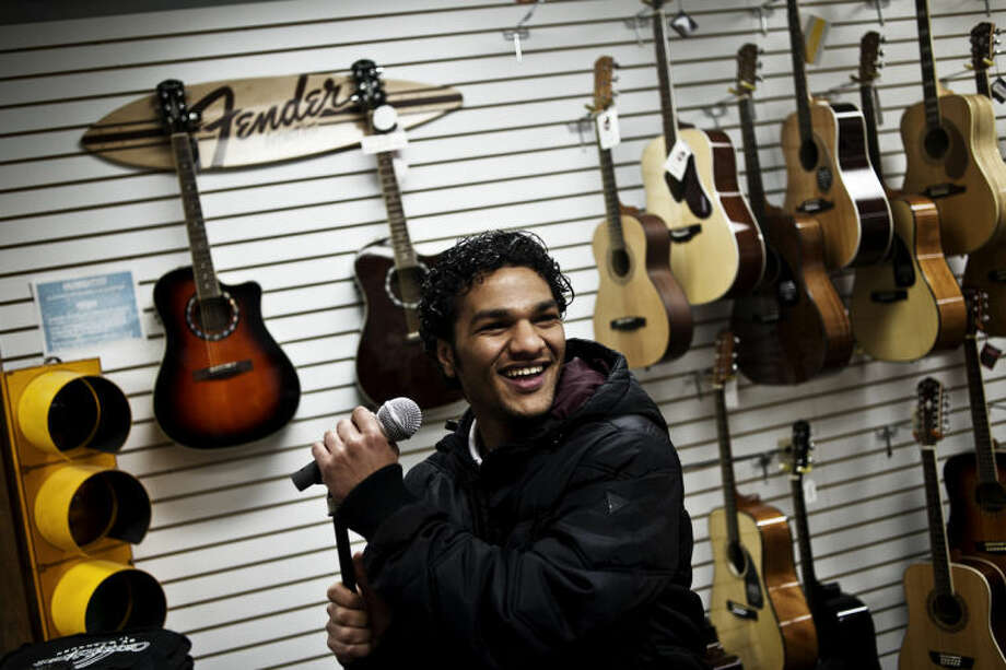 SEAN PROCTOR | sproctor@mdn.netAli AlSalem, 28, of Saudi Arabia, jokingly sings into a microphone at Mid Michigan Music during a scavenger hunt for international students at Saginaw Valley State University in downtown Midland. Sixty-five students spent part of their afternoon looking for certain stores and people or items in those storms to photograph as part of the hunt. The activity helps the students to increase their vocabulary skills. Photo: Sean Proctor/Midland Daily News