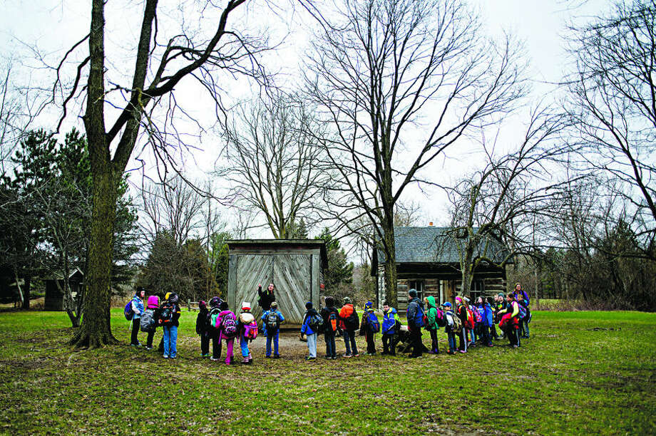 Chippewa Nature Center educator Autumn Foutch tours Pine River Elementary School third graders around the Homestead Farm Thursday at the center. Foutch used the setting to teach the students about rural life in the 1870s. Each day this week the students learned about different eras in history at the nature center. Photo: Nick King Midland  Daily News