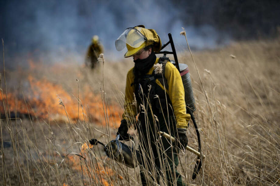 PlantWise LLC employee Cayla Tinney lights an area of grass on fire during a prescribed burn on the Chippewa Nature Center's land on Wednesday. Photo: Neil Blake/Midland Daily News
