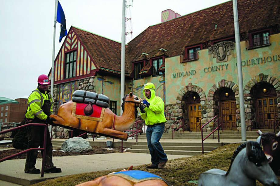Gerace Construction workers Allen McNier, left, and Matt Robbins haul a camel from the Midland County Courthouse nativity set to a trailer as they pack up the Christmas decorations on Thursday. McNier said that the frozen ground made it difficult to pack up the set. Photo: Neil Blake/Midland  Daily News