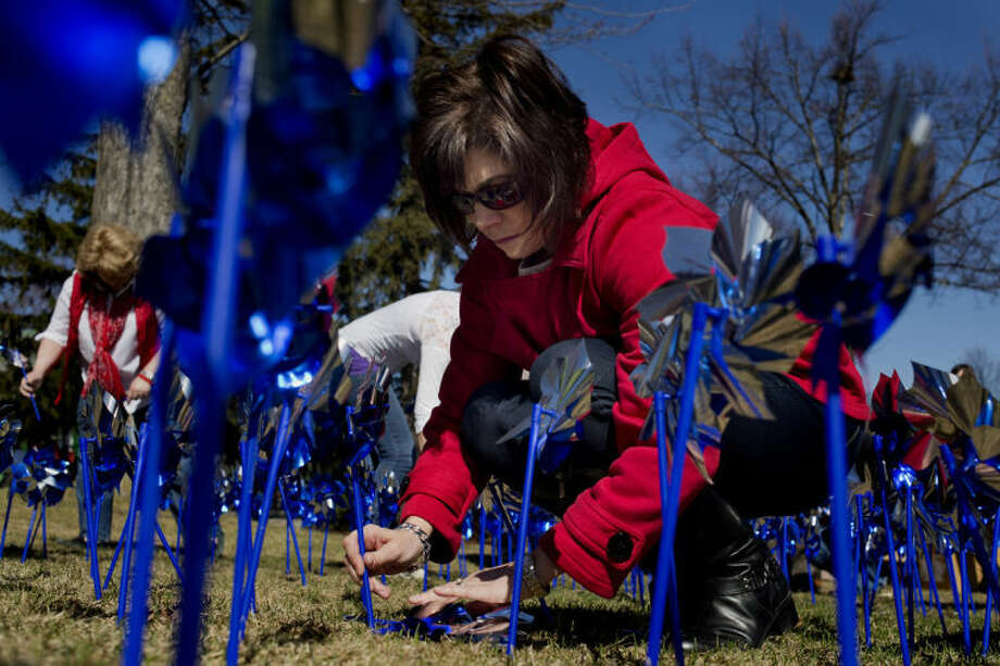 "Bridgette Gransden, the Midland County Administrator Controller, plants a pinwheel in honor of National Child Abuse Prevention Month at the Midland County Courthouse on Friday. The pinwheels will be in front of the courthouse through the end of the month. ""Pinwheels represent a happy childhood and a healthy childhood,"" Nicki Smith, Executive Director at Safe and Sound Child Advocacy Center, said. ""It only takes one person one time to do something to help a child."" Photo: Neil Blake/Midland  Daily News"