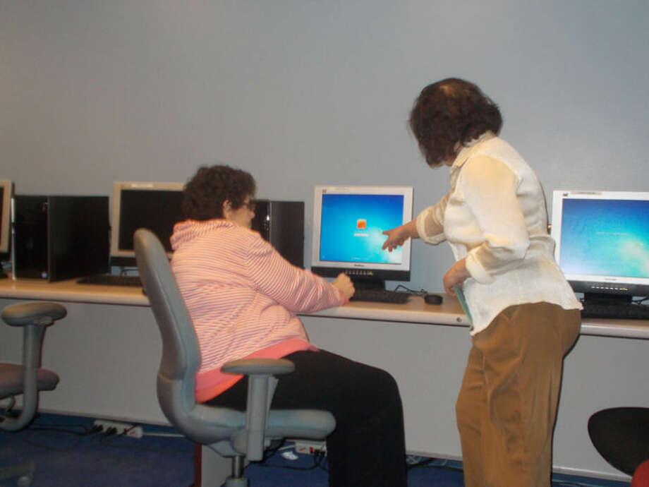 Collaboration WMFC style: Council on Aging Senior Services staff member, Tammy Jerome, (right) helps patron Connie Billingsley at the WMFC computer lab … computers provided by St. John's Episcopal Church. Photo: Photo Provided