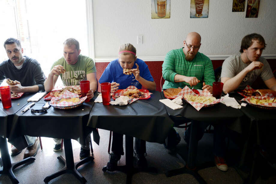 NICK KING | nking@mdn.netFrom left, Ron Berry, Shane Riggie, Ann Hamlin, Ken Herkel and Travis Nelson work on eating their three-and-a-half pound Fool's Gold Loaf sandwiches Saturday at Annabelle's Own. Seven people participated in the one-hour challenge of eating the peanut butter, jelly and bacon sandwich and potato chips, which was one of Elvis' favorites. Ann Hamlin, 20, of Grayling, won the competition.