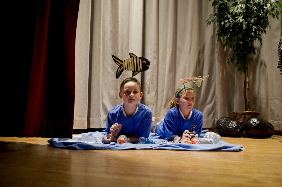 "Blessed Sacrament third-graders Kevin Groulx and Elaine Dunsmore act out their roles as fish in the Earth Day play entitled ""The Picnic"" on Tuesday. The third-graders, all in Debbie Waltz's class, performed the play for parents and the student body. The play encouraged stewardship of the Earth. Photo: Neil Blake/Midland Daily News"
