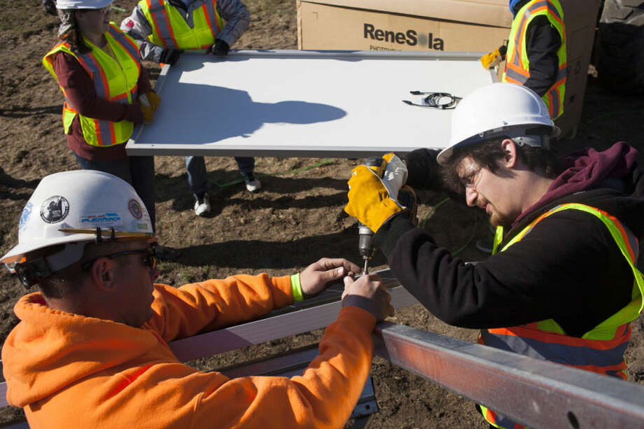 ZACK WITTMAN   for the Daily NewsRobert Bidner, of Livonia, helps tighten the frame of a solar array with the help of J. Ranck Electric employee Jason LeCureux at a hands-on solar energy workshop Wednesday. Photo: Zack Wittman