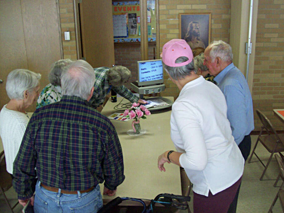 Photo providedSupport group members watch as a reader machine is demonstrated.