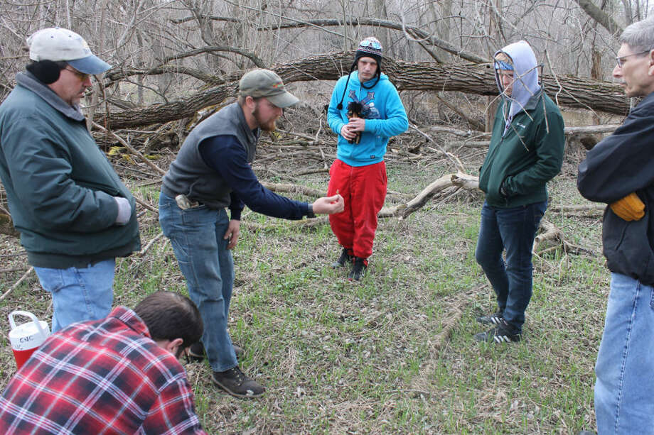 A Chippewa Nature Center employee shows a group of volunteers what the evasive exotic plant called garlic mustard looks like in this Daily News file photo.