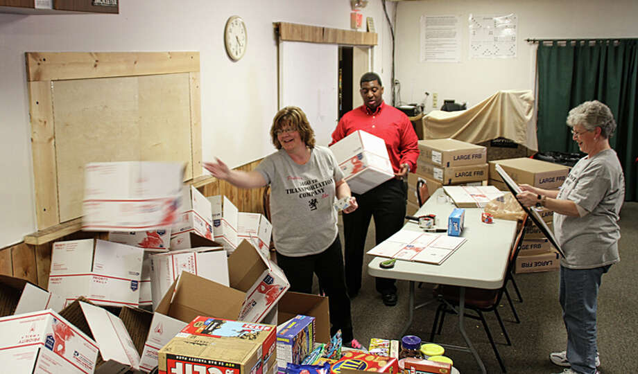 Beth Von Hinken, right, looks on as another volunteer tosses an assembled box while working with Dow Chemical Co. employee T.J. Pope on Thursday. Photo: Photo Provided