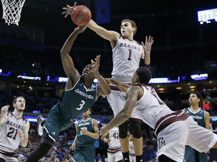 Texas A&M forward D.J. Hogg (1) knocks the ball away from Green Bay guard Khalil Small (3) as Small is fouled by guard Anthony Collins (11) in the second half of a first-round men's college basketball game in the NCAA Tournament, Friday, March 18, 2016, in Oklahoma City.