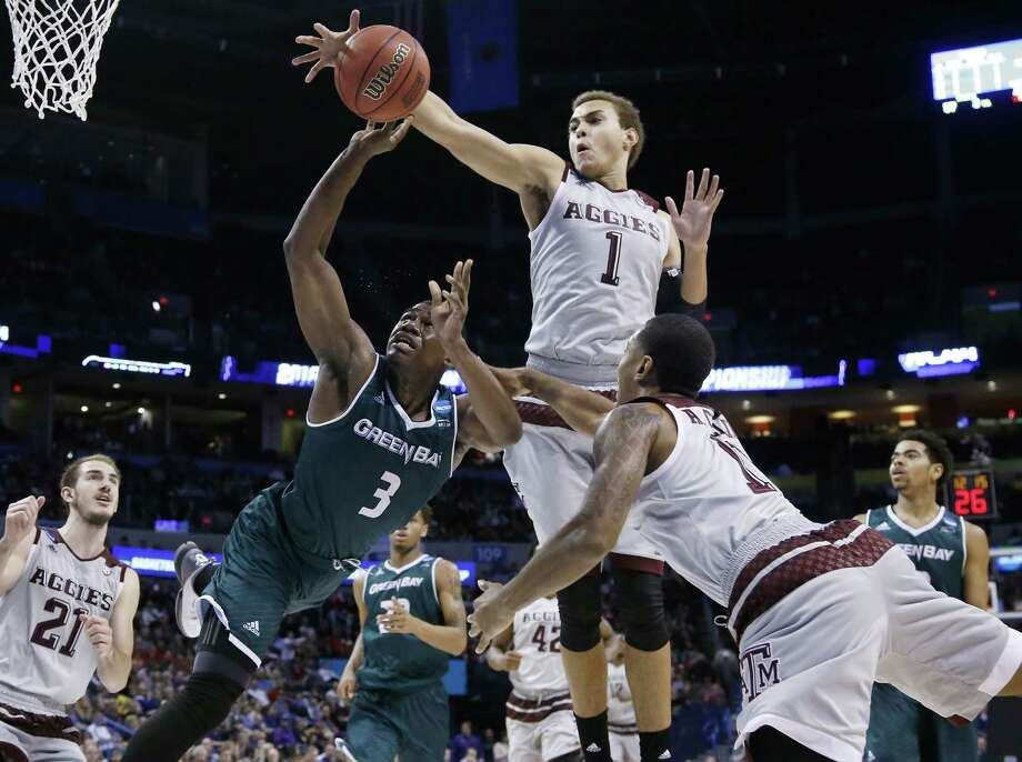 Texas A&M forward D.J. Hogg (1) knocks the ball away from Green Bay guard Khalil Small (3) as Small is fouled by guard Anthony Collins (11) in the second half of a first-round men's college basketball game in the NCAA Tournament, Friday, March 18, 2016, in Oklahoma City. Photo: Sue Ogrocki, AP / AP