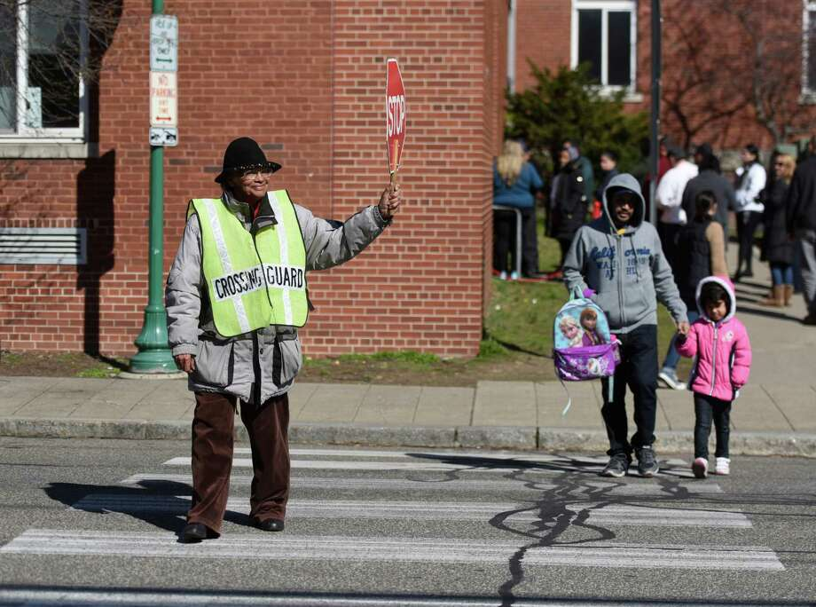 Crossing guard Fredena Johnson assists folks crossing the street outside of Hart Magnet School on Adams Avenue in Stamford, Conn. Monday, March 21, 2016. There are currently about 90 crossing guards in the city and the mayor is making a push to raise their wage from $11.90/hour to $15/hour over three years. Photo: Tyler Sizemore / Hearst Connecticut Media / Greenwich Time