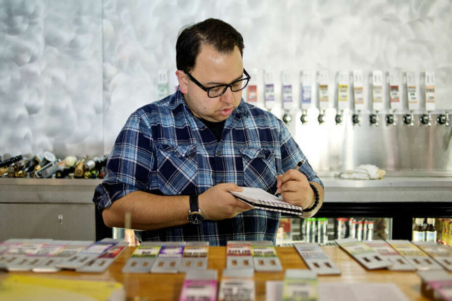 NICK KING | nking@mdn.netManager Russell Kela organizes tap handles at WhichCraft Taproom as he and other employees prepared for a recent tap takeover. Photo: Nick King/Midland  Daily News