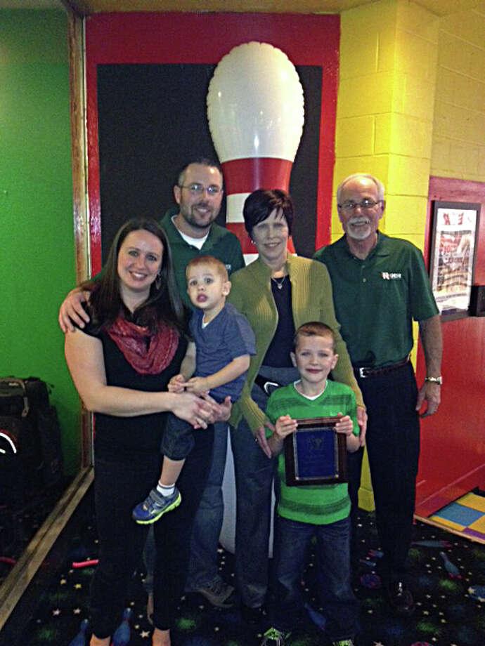 Photo providedFrom left, Amanda Stevens (holding Charlie Stevens), Joel Stevens, Peggy Stevens, Jay Stevens (holding plaque), and Chris Stevens are the Midland Bowling Family of the Year.