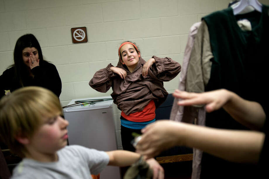 NICK KING | nking@mdn.netLuca Jolly, 11, right, and Jamie Miller, 10, try on costumes as Jolly's mother, Kelli, background left, looks on during a rehearsal of Les Misérables Tuesday at the Midland Center for the Arts. Luca is playing the part of an urchin and Jamie is playing the part of Gavroche. Kelli is doing  choreography for the production. Photo: Nick King/Midland  Daily News