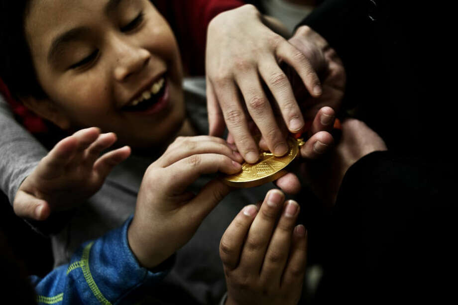 SEAN PROCTOR | sproctor@mdn.netAdams Elementary students touch the 2008 Olympic Gold medal belonging to retired swimmer Peter Vanderkaay after he spoke to them during a morning assembly on Thursday. Photo: Sean Proctor/Midland Daily News