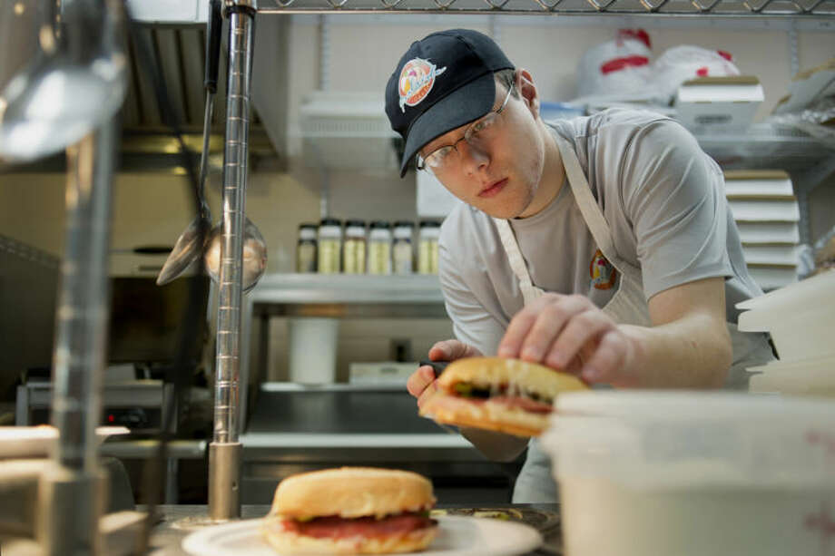 NEIL BLAKE | nblake@mdn.netBrandon Toner of Coleman moves a grinder on to a plate to serve at the Poolside Cafe in the Midland Community Center on Thursday. The cafe, which has been open since late last year, serves a variety of personal pizzas, grinders and salads. Photo: Neil Blake/Midland  Daily News