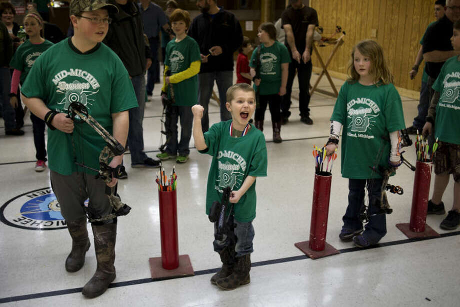 "NEIL BLAKE | nblake@mdn.netEthan Bovee, 5, of Coleman, shouts ""Yes!"" after finding out he won a prize in a drawing at the final Mid-Michee Bowmen winter league youth shoot in Midland on Friday. Seconds earlier he said to his father, ""Why can't he pick a 644?"" Photo: Neil Blake/Midland  Daily News"