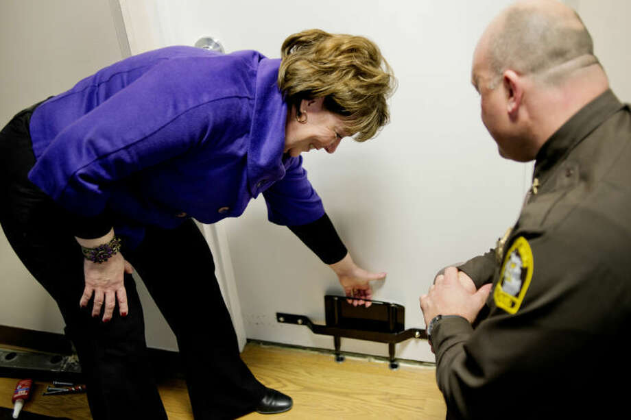 NICK KING | nking@mdn.netShelterhouse Executive Director Janine Ouderkirk, left, tries out The Boot safety device as Midland County Sheriff Scott Stephenson looks on Wednesday. The creator of The boot and Stephenson were on hand for the installation of the device. Photo: Nick King/Midland  Daily News