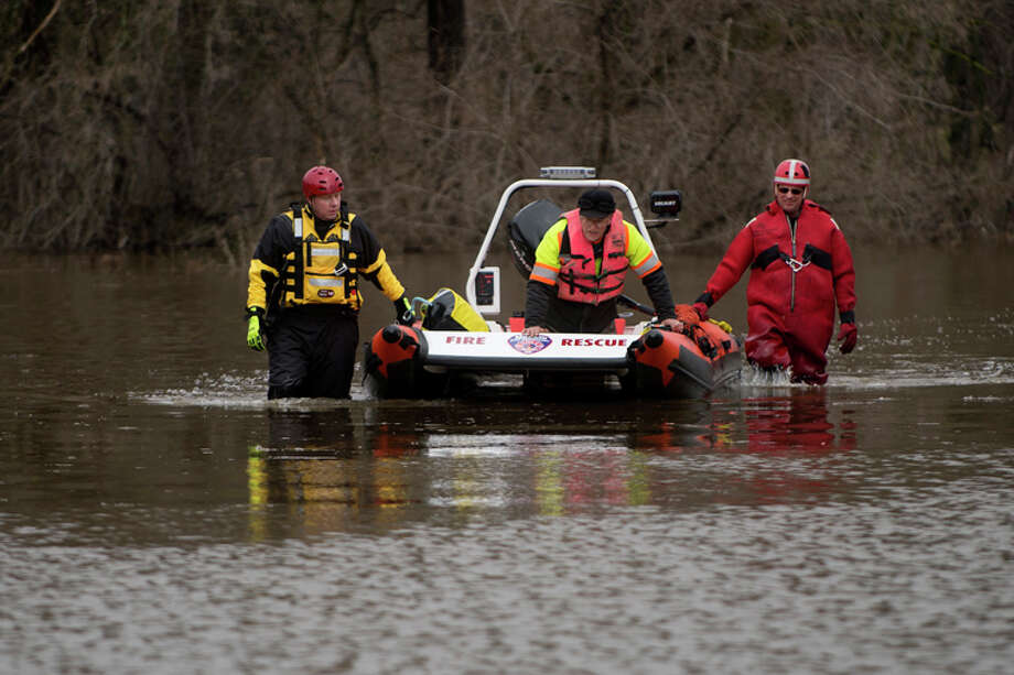 FILE PHOTOMidland Fire Department firefighter Ryan Bebeau and Lt. John Day walk next to their boat carrying Midland city worker Charles Barto during flooding in April 2013. Barto needed to work in an area near Currie Parkway that was inaccessible because of the flooding.