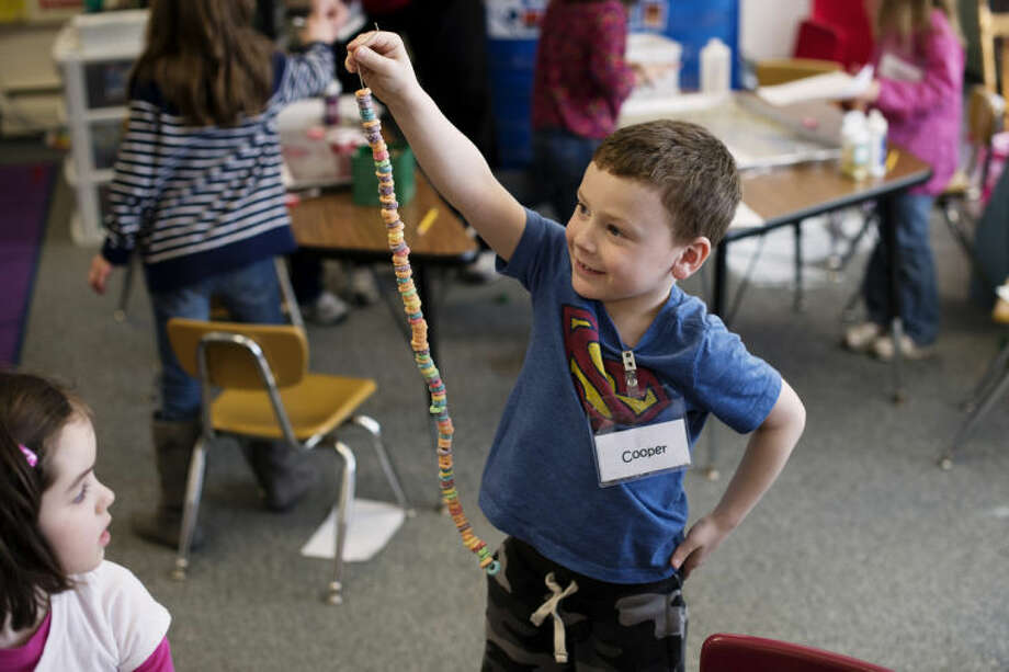 NEIL BLAKE | nblake@mdn.netCooper Cummings holds up a Fruit Loop necklace in a kindergarten class on Wednesday during Chestnut Hill Elementary School's 100th day celebration. Photo: Neil Blake/Midland  Daily News