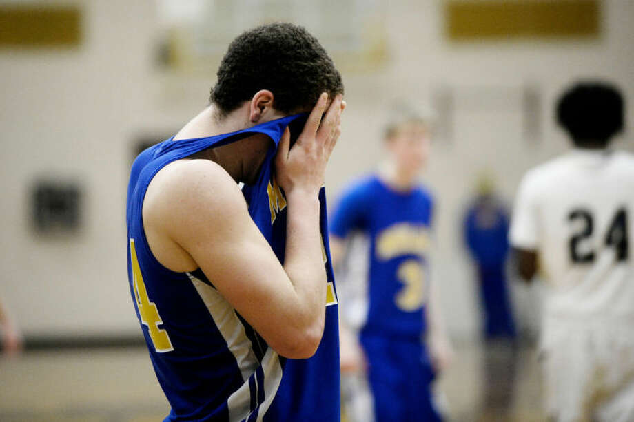 SEAN PROCTOR | sproctor@mdn.netMidland's Zachary Stirn holds his jersey up to his face after time expires against Mount Pleasant Wednesday during their Class A district game at Bay City Western. Midland lost to Mount Pleasant 57-51. Photo: Sean Proctor/Midland  Daily News