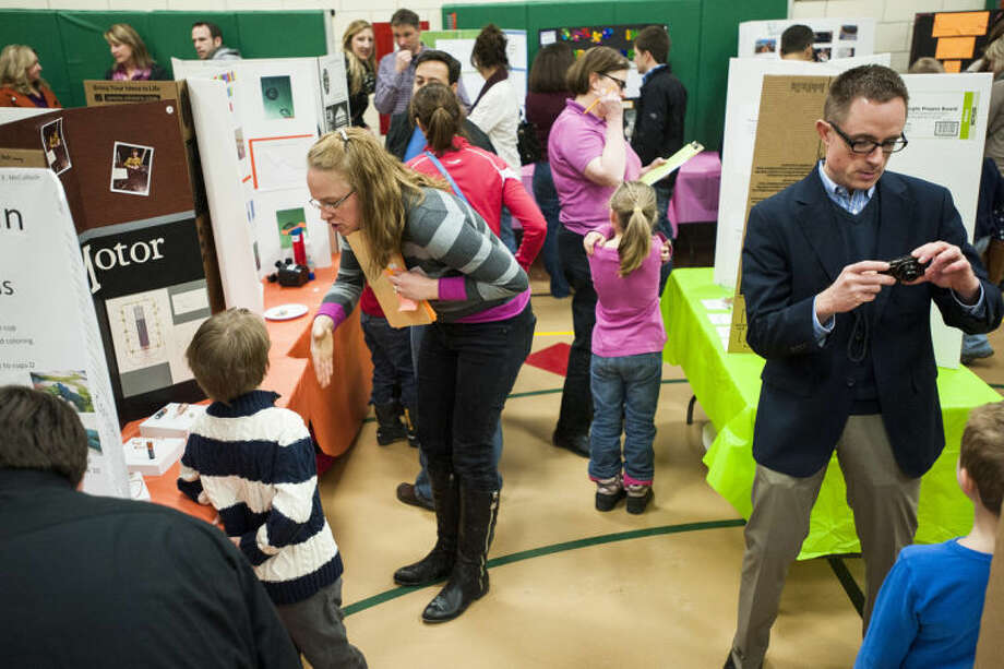 ZACK WITTMAN | for the Daily NewsJudges wander around the gymnasium while parents take photos of their young scientists during Siebert Elementary School's annual science fair. Photo: Zack Wittman