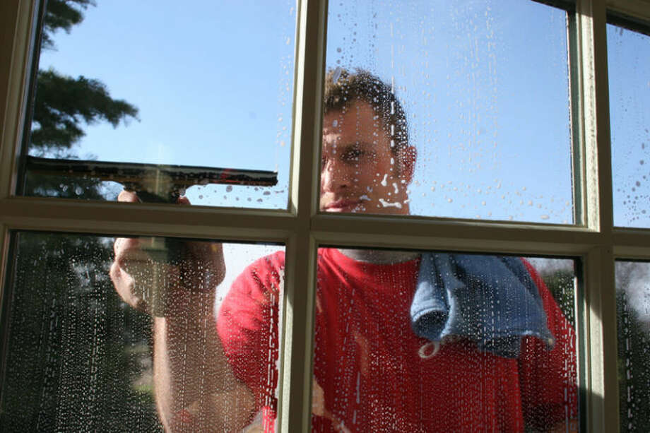 Aaron Haarsma, owner at Shine Window Care of Grand Rapids, cleans a window. Photo provided Photo: Unknown