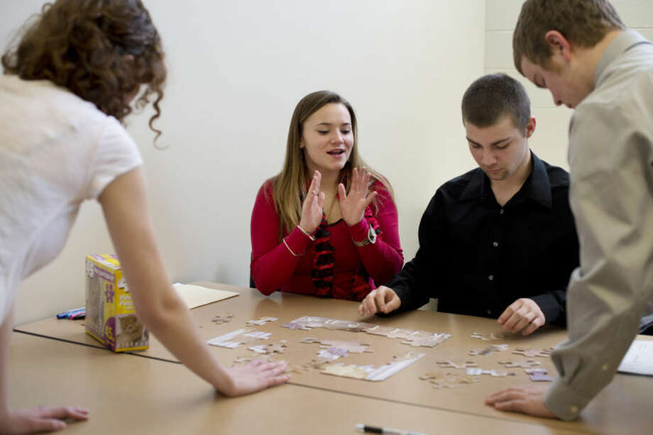 "NEIL BLAKE | nblake@mdn.netETC Junior Kirstyn Piotrowski, center, works with Dow senior Estelle Wisniewski, left, ETC senior Lucas Hoover, center right, and Dow junior Wesley Blackmore, far right, to put together a puzzle at the ""Ready, Set, Get Hired!"" event at Davenport University. Another group had a few of the pieces that were needed to complete the puzzle to demonstrate the need for cooperation between departments. Photo: Neil Blake/Midland  Daily News"