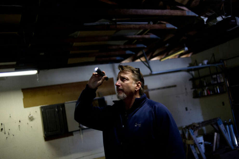 NICK KING | nking@mdn.netElliot Environmental mold removal's Brian Carson checks the attic for mold from the garage of a vacant home while searching the property Friday in Bay City. Photo: Nick King/Midland  Daily News