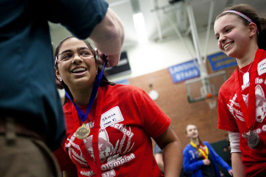 ZACK WITTMAN | for the Daily NewsJefferson Middle School's Shreya Nagarkar, 13, smiles with her classmate, Isabel Chaput, 12, while accepting a first place medal during the Region IV Science Olympiad at Delta College on Saturday afternoon. The two seventh-graders helped their school finish second place overall in the middle school division, sending the team to the statewide Olympiad in East Lansing.