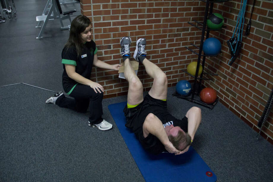 EMILY BROUWER | for the Daily NewsLauren Hayes, 24, of Midland, helps Paul White, 56, of Midland, with crunches during a training session at the Midland Community Center. Hayes is the lead trainer for White and has been working with him for the past year.