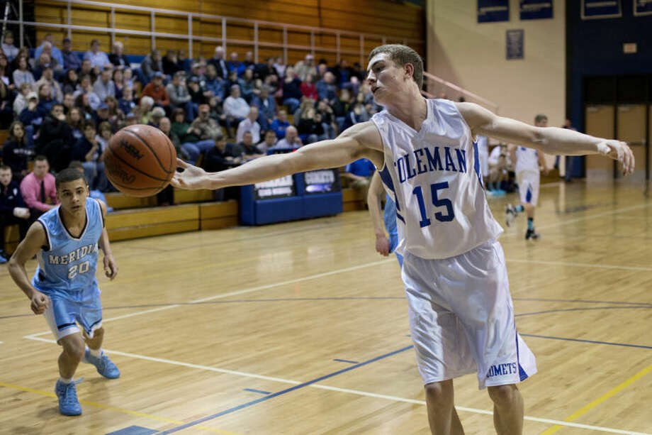 NEIL BLAKE | nblake@mdn.netColeman's Jarid Walton reaches for the ball as Meridian's Jacab Ham looks on at Coleman High School on Monday. Photo: Neil Blake/Midland  Daily News